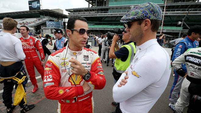 Helio Castroneves, left, talks with Townsend Bell, right, May 18, 2015 at the Indianapolis Motor Speedway.