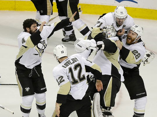 Pittsburgh Penguins players celebrate around goalie Matt Murray, center, after beating the San Jose Sharks in Game 6 of the NHL hockey Stanley Cup Finals in San Jose, Calif., Sunday, June 12, 2016. The Penguins won 3-1 to win the series 4-2.