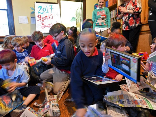 Children rip into their presents at the Renzi Education and Art Center 2017 Christmas party.