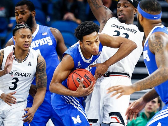 Memphis guard Jamal Johnson (middle) grabs a rebound