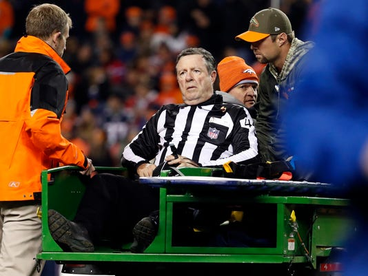 Umpire Jeff Rice is carted off the field after New England Patriots linebacker Trevor Reilly accidentally hit him on a play during the second half of an NFL football game against the Denver Broncos, Sunday, Nov. 12, 2017, in Denver. (AP Photo/Jack Dempsey)