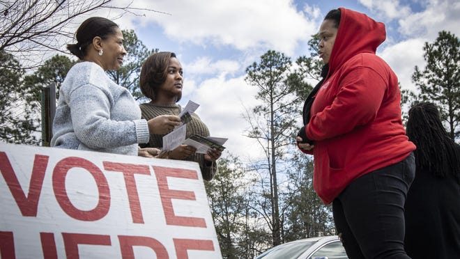 At left, Brenda Mitchell and her daughter, Kiana Mitchell, listen as campaign worker Kia McMillan tries to persuade them to reelect Cumberland County District Court Judge Lou Olivera. They were at the early voting polling site at the North Regional Branch of the Cumberland County Public Library on Feb. 29, the last day of early voting in the 2020 primaries.