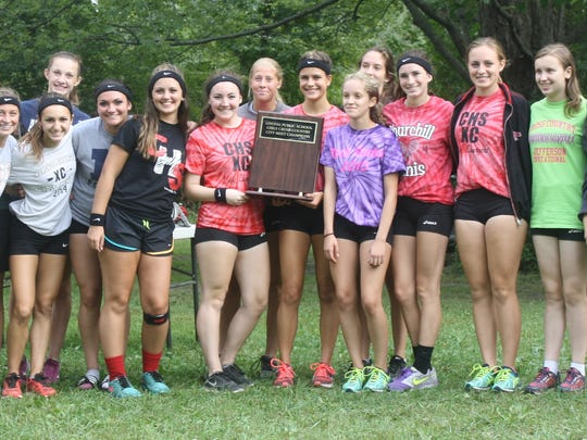 Members of Churchill's cross country team pose with their first-place trophy.