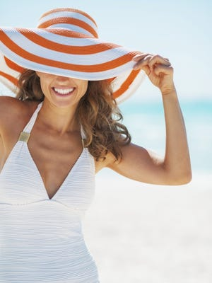 Portrait of happy woman in swimsuit hiding behind beach hat.