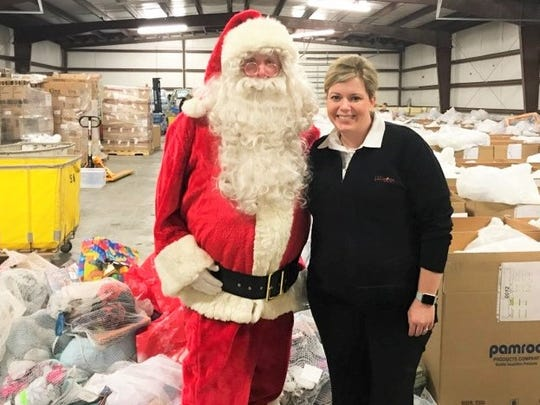 Lt. Laura Gesner takes a photo with Santa Claus amid donated clothing and supplies that will be distributed this holiday season.