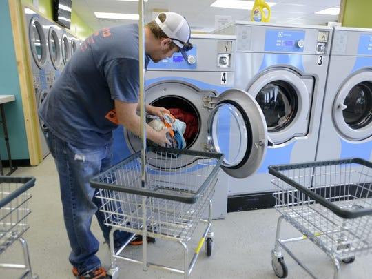 Phillip Peterson of Colchester takes his laundry out of the washer on Tuesday afternoon at Clothes Quarters Laundromat in Winooski.