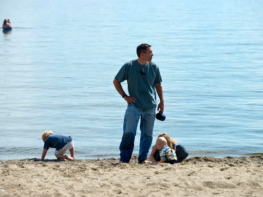 James Ehlers with his children Edward, Frederick and Lillian at North Beach in Burlington on Wednesday.