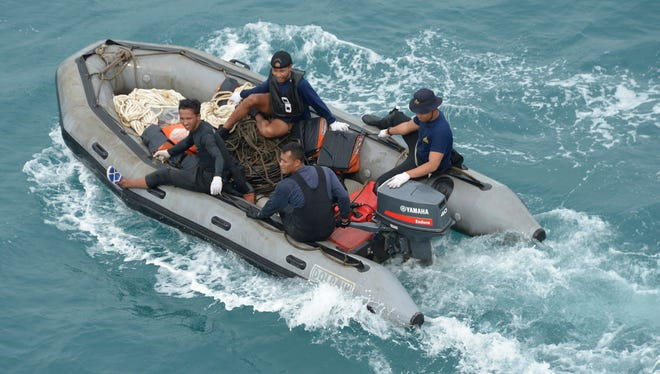 Indonesian navy divers arrive on boats after conducting operations to lift the tail of AirAsia Flight 8501 in the Java Sea.