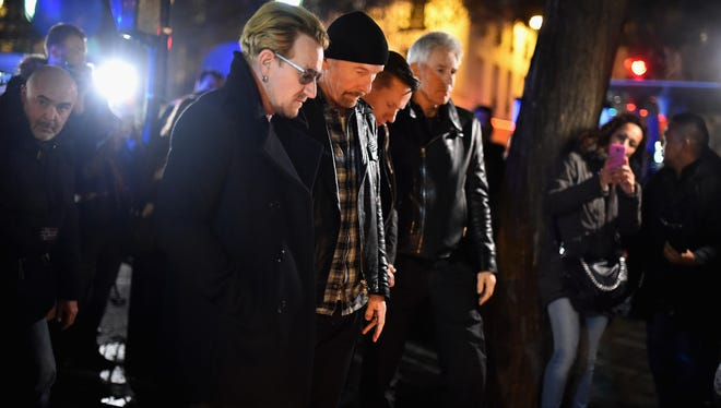 U2 pay their respects and place flowers on the pavement near the scene of yesterday's Bataclan theater attack.