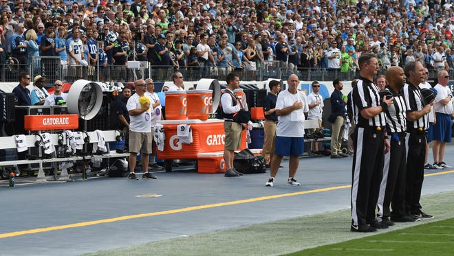 The officials during the national anthem with a Seahawks bench without players or coaches prior to the beginning of the game at Nissan Stadium Sunday, Sept. 24, 2017 in Nashville, Tenn.