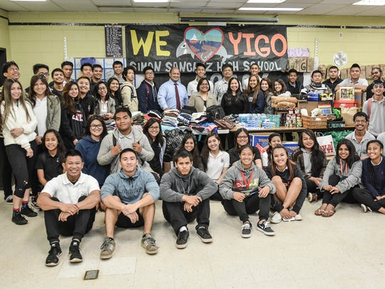 """Students from Simon Sanchez's English 12 Legacy class gather around their collected donations of food, clothing, and household supplies for victims of Typhoon Dolphin on May 28. Standing with the students are Superintendent Jon Fernandez, who rewarded the group with a $100 check, and Yigo Mayor Rudy Matanane, who received the donations on behalf of his village. Luke Fernandez, Legacy president and Sanchez senior, thanked his teacher Mrs. Acie Jo cruz for inspiring the group to take action. """"We knew we had to do something because this is our school, and this is our community,"""" said Fernandez."""