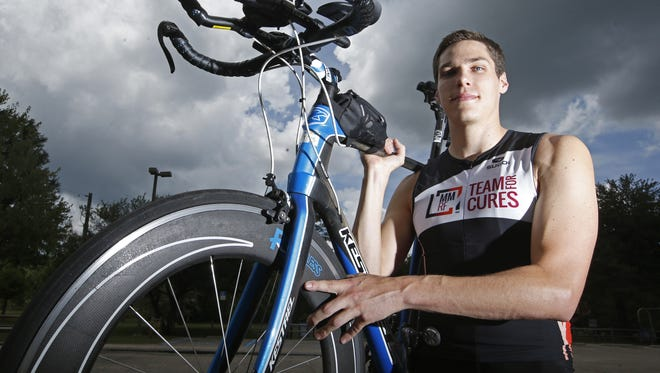 Jason Hohensee holds the bike that he rode in 2015, his first complete Ironman competition, which involves a 2.4-mile swim, 112-mile bike ride and full marathon, a 26.2-mile run.