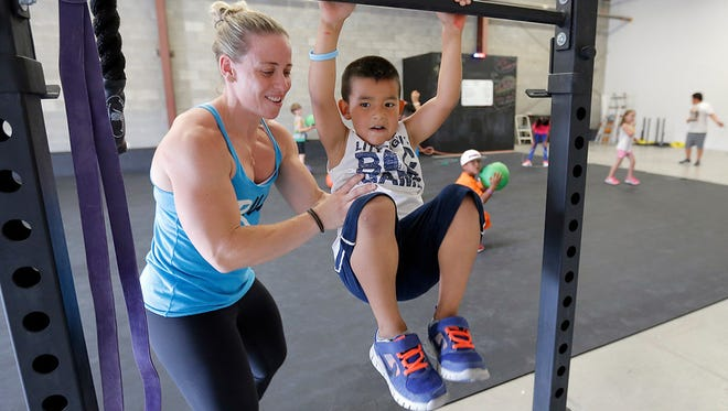 Former UTEP soccer player Holly Cohen Mata helps Brayden Reyna, 6, with a Crossfit drill during her Kids Crossfit class Monday at Get Lifted, 4725 Ripley. ""