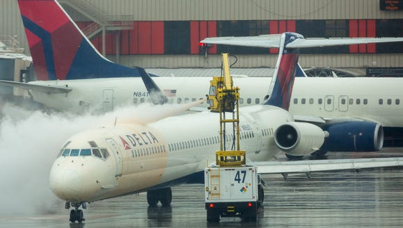 A Delta Air Lines jet is treated with de-icing fluid