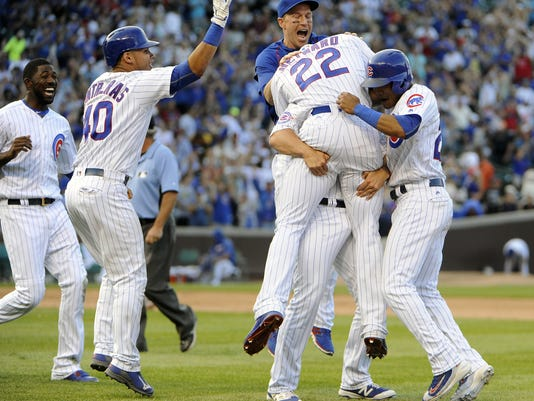 Chicago Cubs' Jason Heyward (22) celebrates with teammates after hitting a winning single against the San Francisco Giants during the thirteenth inning of a baseball game, Sunday, Sept. 4, 2016, in Chicago. (AP Photo/David Banks)