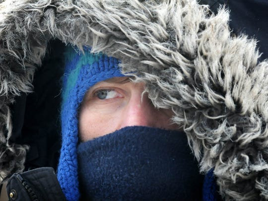 Jeremy Jaspers of Mankato is bundled up against Monday's sub-zero temperatures while walking downtown. Adding snowy insult to frigid injury, the National Weather Service is predicting as much as 6 inches of new snow overnight over much of southern Minnesota.