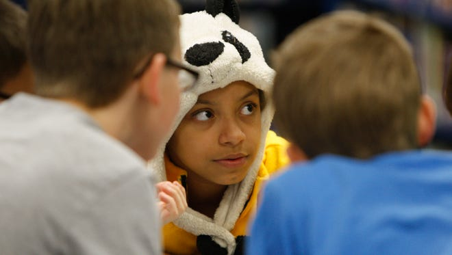 Fifth-grader Rebecca Estrada, wearing her panda hat, joins with her Odyssey of the Mind team in problem solving exercises last month.