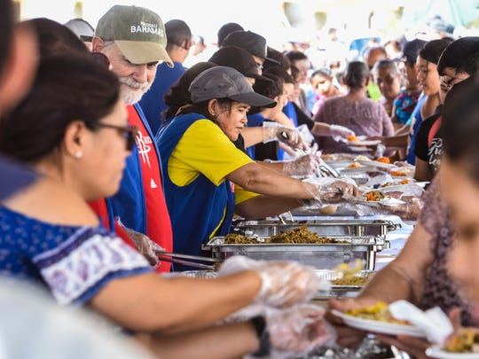 Volunteers take the time to serve meals to some of the island's less fortunate residents during The Salvation Army's annual Thanksgiving Day feast behind the Chamorro Village in Hagåtña on Thursday, Nov. 23, 2017.