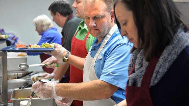Premier Real Estate Services employee Noel Johnson, center, waits to add food to a tray while serving lunch Monday, Nov. 23 at the St. Cloud Salvation Army Shelter. Premier has provided and served lunch each Monday in November this year as part of the PhilanthroFEED program.