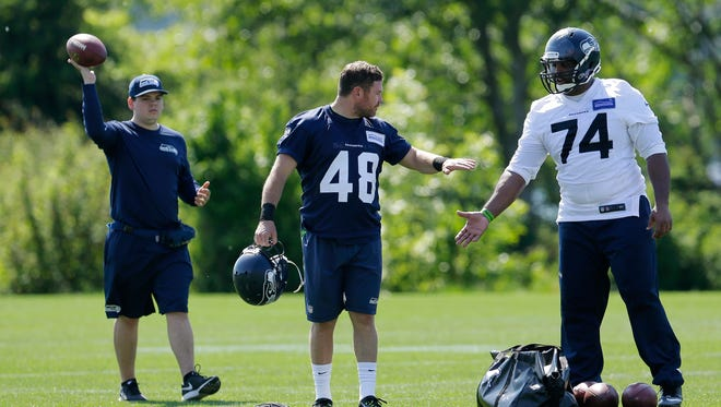 A member of the Seattle Seahawks equipment staff, left, holds a football as U.S. Army veteran and former Texas long snapper Nate Boyer (48) greets defensive end Julius Warmsley, right, after taking part in drills at Seattle Seahawks NFL football rookie minicamp, Friday, May 8, 2015, in Renton, Wash.
