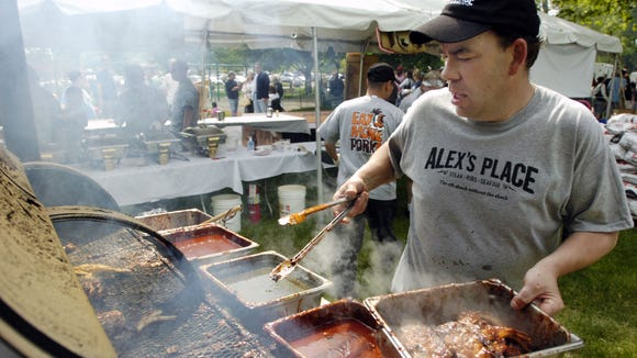 Alex's Place rib cook Tim Greene of Batavia  pulls racks of ribs off the pit for customers during the 2nd annual Roc City Rib Fest, in 2009.