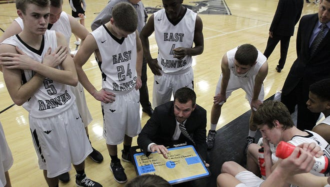 Coach Clint Adkins goes over some last-minute strategy before his Lakota East Thunderhawks take the court Dec. 9.