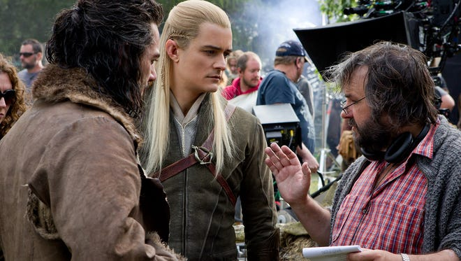 """Luke Evans, left, Orlando Bloom and director Peter Jackson on the set of """"The Hobbit: The Battle of the Five Armies."""""""