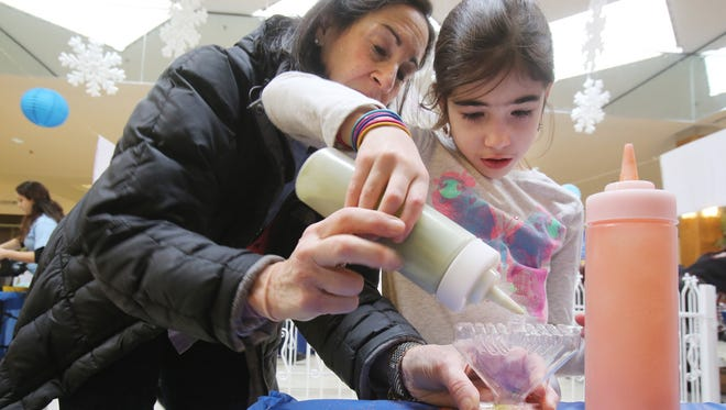 """Grandmother Robin Rosenbaum of Teaneck, N.J., left,  gives her granddaughter Nava Feldman, 7, of Huntington Woods a hand as she pours  colorful sand into a menorah that can be worn as a necklace during """"Chanukah Wonderland,""""  a celebration  at Orchard Mall, Sunday, Dec. 21, 2014."""