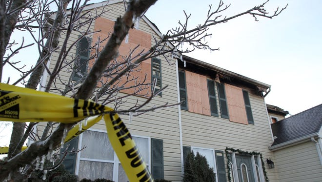 Police tape hangs from an ice encrusted tree outside 92 Cascades Avenue in Howell Township Wednesday morning, December 31, 2014.  A late night fire Tuesday left the home heavily damaged.    HOWELL TOWNSHIP, NJ   HOWELLFIRE1231A    STAFF PHOTO BY THOMAS P. COSTELLO