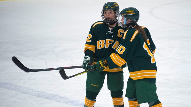 BFA-St. Albans defensemen Maddy Dean, left, and Makenna Larrow talk before the puck drops at the start of Saturday's game against South Burlington.