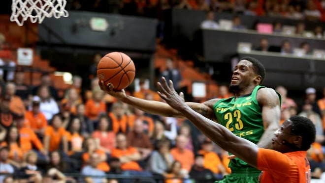 "Oregon's Elgin Cook (23) extends for the hoop as Oregon State's Daniel Gomis (14) tries to defend in the second half of the Oregon vs. Oregon State ""Civil War"" men's basketball game in Corvallis on Wednesday, March 4, 2015. The Ducks won the game 65-62."
