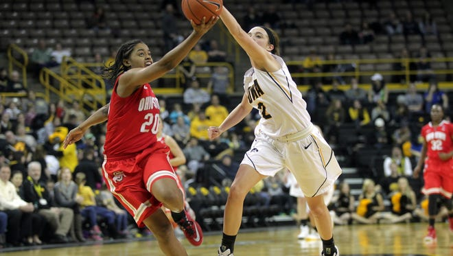 Iowa's Ally Disterhoft and Ohio State's Asia Doss chase down the ball during their game at Carver-Hawkeye Arena on Thursday, Feb. 5, 2015.    David Scrivner / Iowa City Press-Citizen