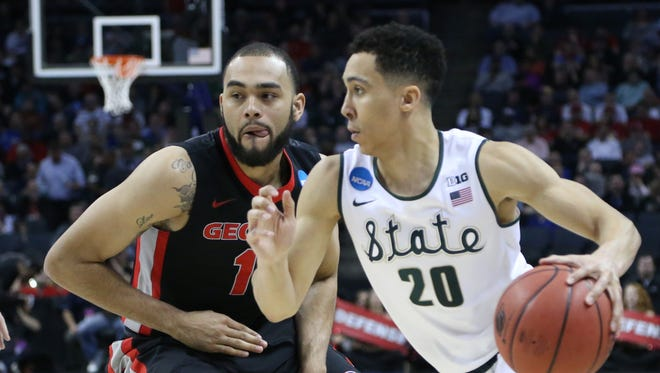 Michigan State's Travis Trice drives against the Georgia Bulldogs' Cameron Forte during second half action of their second round NCAA tournament game March 20, 2015 in Charlotte.