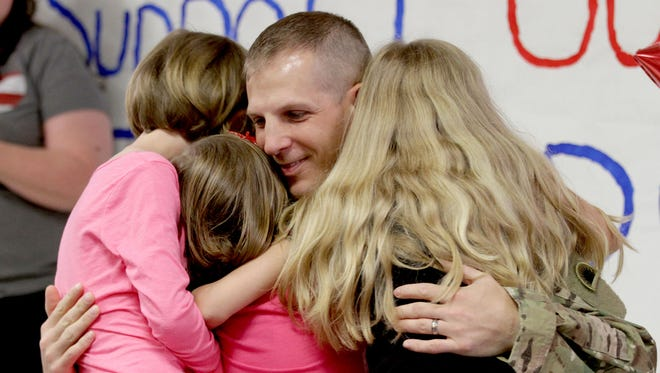 Army Sgt. 1st Class Matthew McCreery hugs his daughters, Sierra, 10, Kinley, 8, and Ashlyn, 6, after surprising them during a Memorial Day assembly at Brush College Elementary School in West Salem on Thursday, May 21, 2015. McCreery just returned from a year-long deployment in Afghanistan.