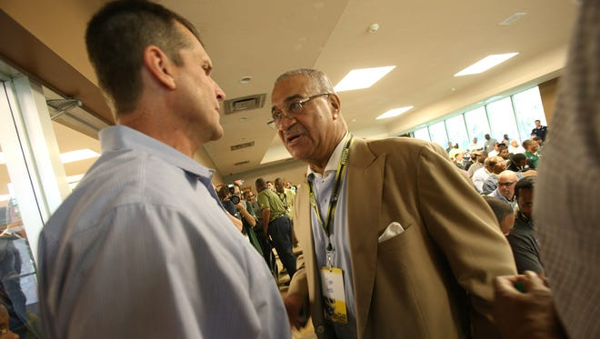 Tom Goss, former Michigan athletic director, right, talks with football coach Jim Harbaugh during a clinic at the Horatio Williams Foundation building in Detroit on Wednesday, May 27, 2015.