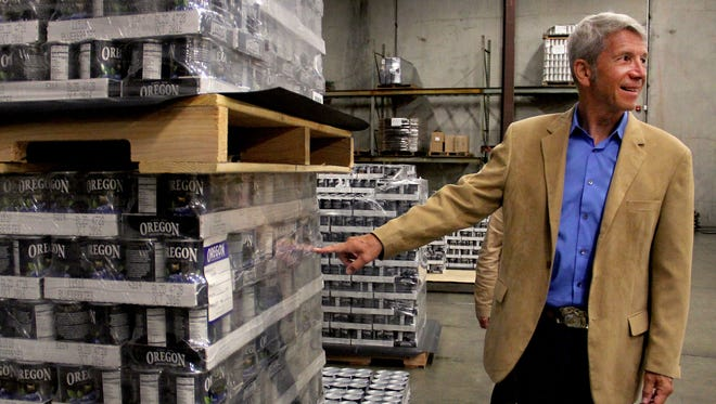Rep. Kurt Schrader points out the label on Oregon Fruit Products cans to be distributed worldwide at Oregon Fruit Products in West Salem on Thursday, May 28, 2015.