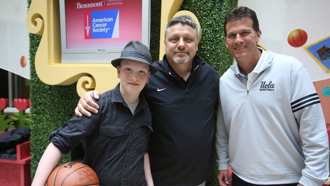 "Kyle Cupp, 13, of Waterford, left, poses with Oakland basketball coach Greg Kampe, center, and UCLA coach Steve Alford during a meet-and greet with college basketball coaches at Beaumont Hospital in Royal Oak as part of the ""Coaches Beat Cancer"" fund-raiser on June 1, 2015."