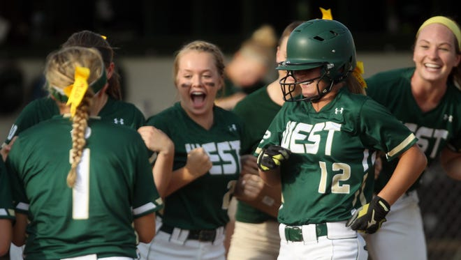 West High's Edie Schwickerath is welcomed at home plate after her home run during the Women of Troy's game against Dubuque Senior on Thursday.