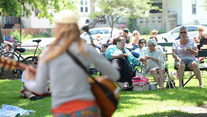 Music lovers eat lunch in Whitney Park as the music group Patchouli plays during the Summer in the Park Music Series.