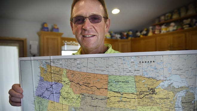 Mike Garland holds a map of his route on the 3,800-mile bike ride from his home to Ashland, Oregon, and back to raise awareness of the American Cancer Society Relay for Life events. The trip took Garland 48 days.