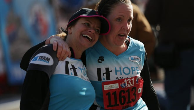 Susan Adams of Troy, MI, left and Deanna Nowakowski of Troy, MI react after finishing the half marathon during the 37th annual Detroit Free Press/Talmer Bank Marathon in Detroit on Sunday, Oct. 19, 2014.