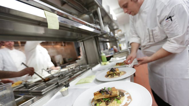 Sous chef Norman Fenton plates during dinner in the kitchen at Bistro 82 in Royal Oak.