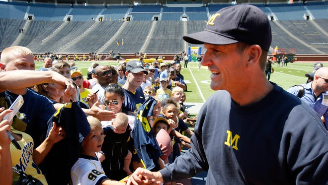 Michigan head coach Jim Harbaugh greets fans as he leaves the field after the team's official photo at Michigan Stadium during football media day on Thursday, August 6, 2015, in Ann Arbor.