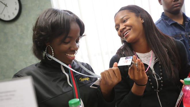 Tanaya Kellom, 16, looks at her new Baker College school ID with classmate Syncere Thurman, 15, both juniors at University High School in Ferndale during the orientation at Baker College's Auburn Hills campus on Tuesday.