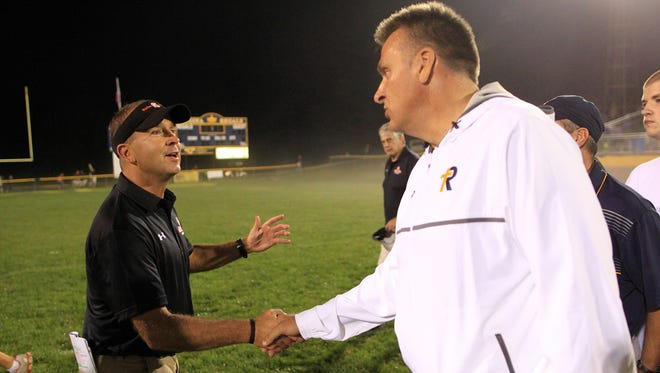 Solon head coach Kevin Miller congratulates Regina head coach Marv Cook after their game at Regina on Saturday, Aug. 29, 2015.