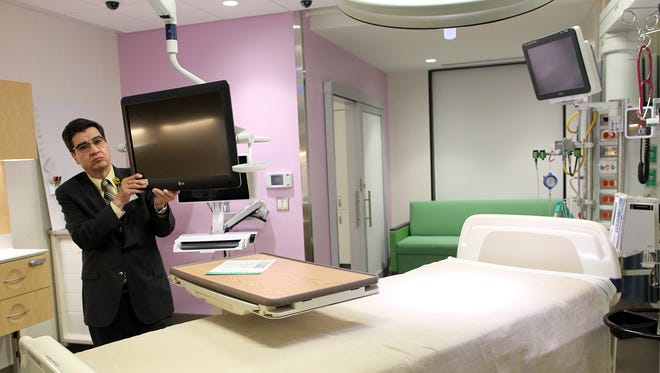 George Mejias, executive director of the University of Iowa Hospitals and Clinics' Capital Management Department, shows off a mock-up of a pediatric intensive care unit room Thursday.   The rooms are modular and largely interchangeable, with the smallest being about 340 square feet.   In addition to the medical supports surrounding the patient's bed or crib, each room also features a family zone, complete with a sleeper large enough for two adults to spend the night.