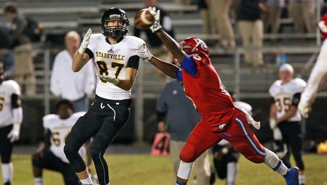 Starkville receiver Luke Davis reaches for a pass around Warren Central safety Byron Galvin Friday night in Vicksburg.
