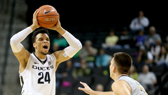 Oregon's Dillon Brooks (24) calls out to his teammates past Northwest Christian's Jay Mayernik (34) in the Northwest Christian vs. Oregon men's exhibition basketball game at the Matthew Knight Arena in Eugene on Tuesday, Nov. 3, 2015. The Ducks won the game 92-44.