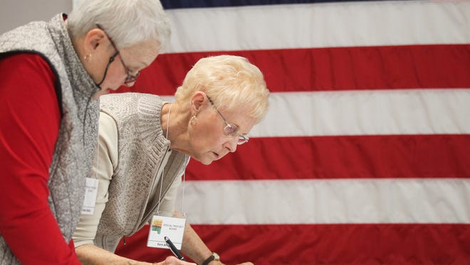 Lorraine Bailey, left, and Fern Allison sort through University Heights voter ballots at the Johnson County Auditor's Office on Thursday, Nov. 5, 2015.