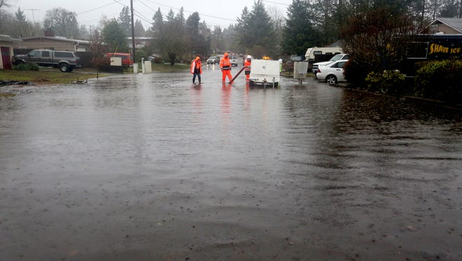 Salem Public Works employees work to unclog a storm drain on Idylwood Drive SE near Liberty Road S in Salem on Monday, Dec. 7, 2015. A flood warning has been issued for Salem until Monday afternoon and a flood watch is in effect through Wednesday afternoon.